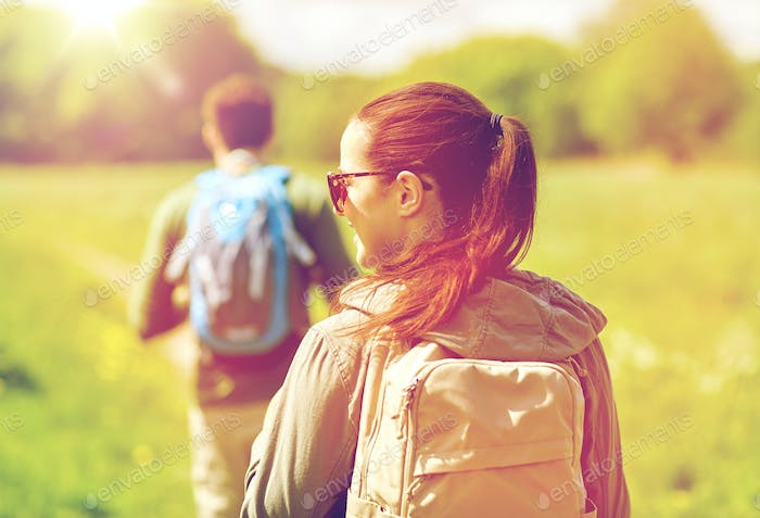 close up of couple with backpacks hiking outdoors