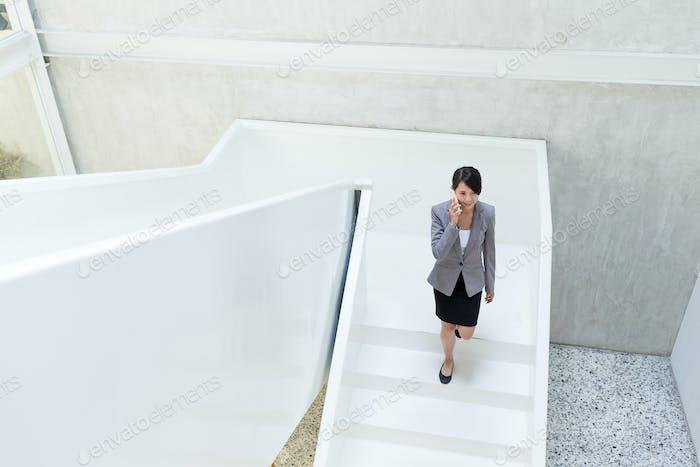 Geschäftsfrau sprechen mit Handy und zu Fuß im Büro