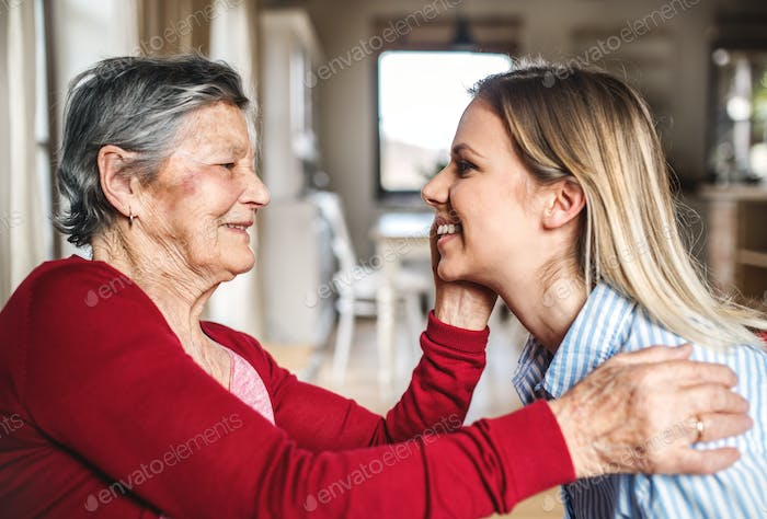 An elderly grandmother looking at an adult granddaughter at home.