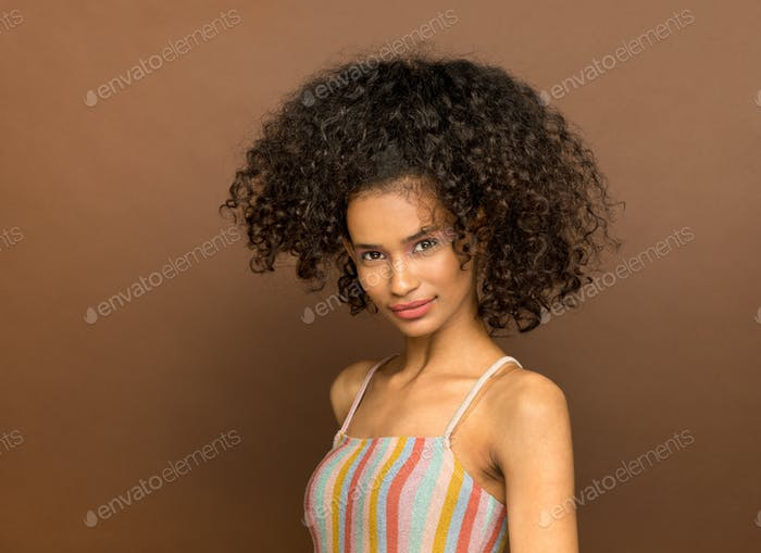 Cute young black woman with curly afro hairstyle