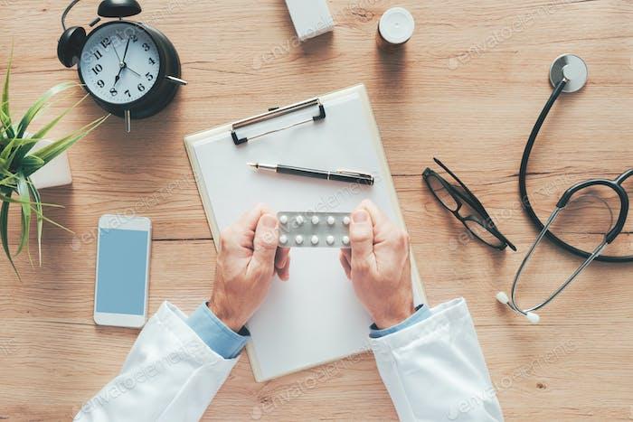 Männlicher Arzt hält unbeschriftet generische Tabletten