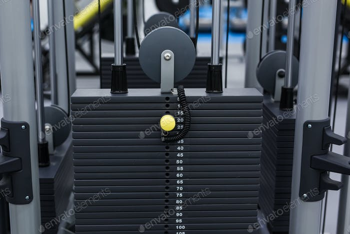 Black iron heavy plates stacked of weight machine in fitness gym. Sports simulator plates