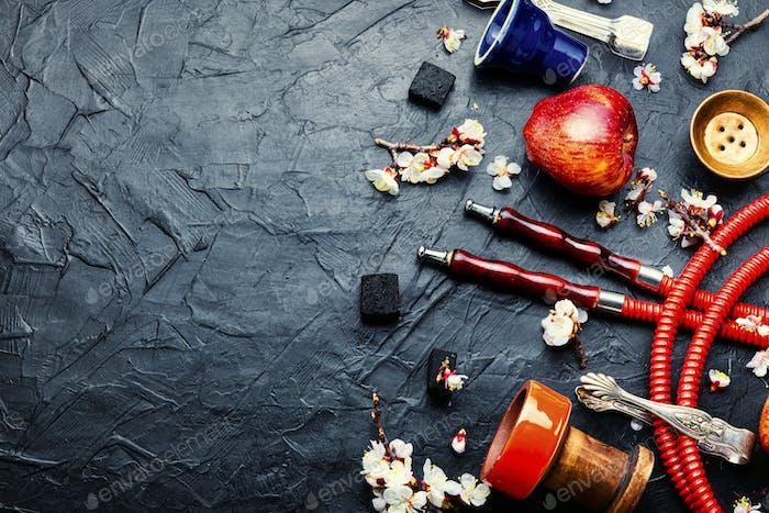 Smoking hookah or shisha with apple flavor