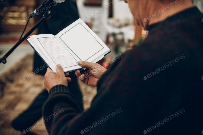 Priester lesen Bibelbuch in der Kirche während der Hochzeitszeremonie