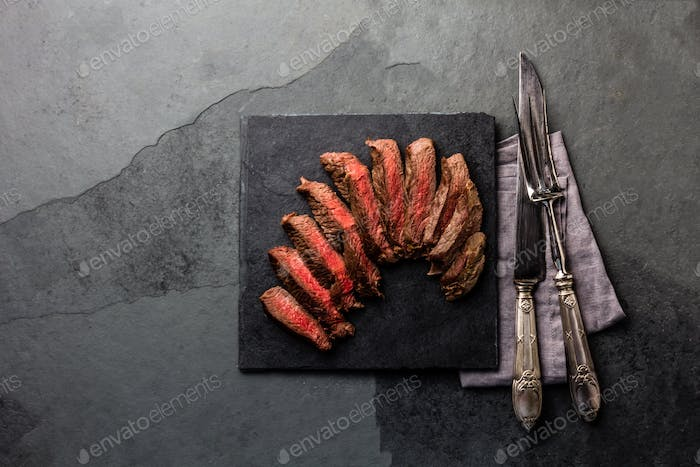 Medium rare beef steak on slate board, vintage cutlery, grey background
