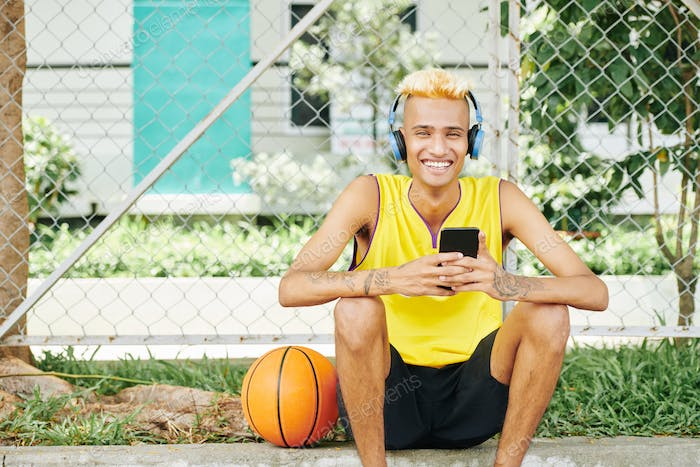 Cheerful basketball player resting outdoors