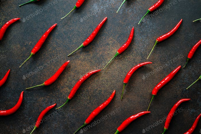 A lot of chili peppers on a kitchen table. Top view.
