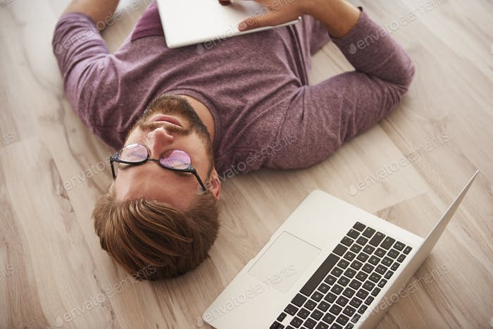 Man lying on the floor with modern technology