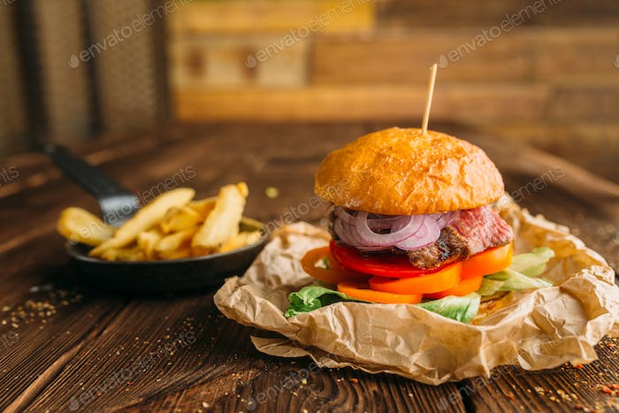 Juice burger with steak on wooden table closeup