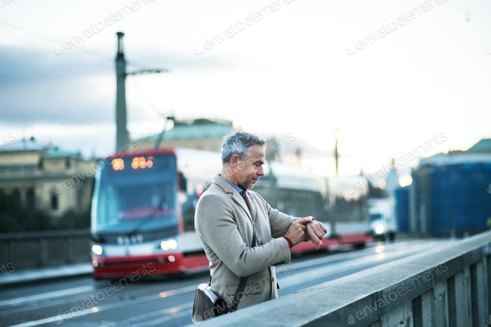 Mature businessman standing on a bridge in Prague city, checking the time.