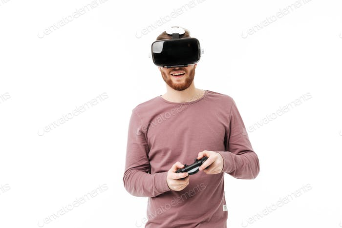 Young smiling man using virtual reality glasses and playing video game over white background