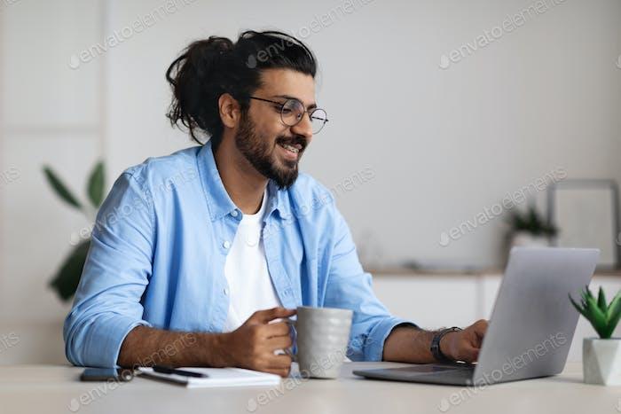 Vorteile von Freelancing. Positive Freelancer Guy trinkt Kaffee und arbeitet am Laptop