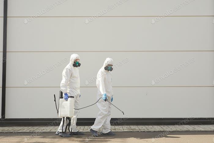 Zwei Desinfektionsarbeiter in der Straße