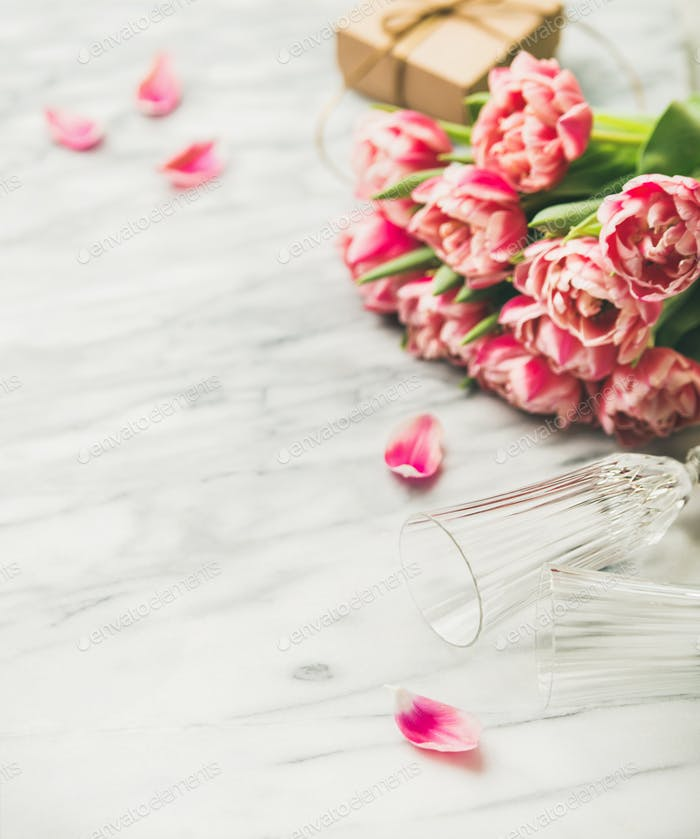 Pink tulips, champaign glasses and gift box with copy space