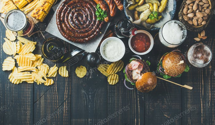 Variety of beers, sausages, burgers, potato, corn on dark background