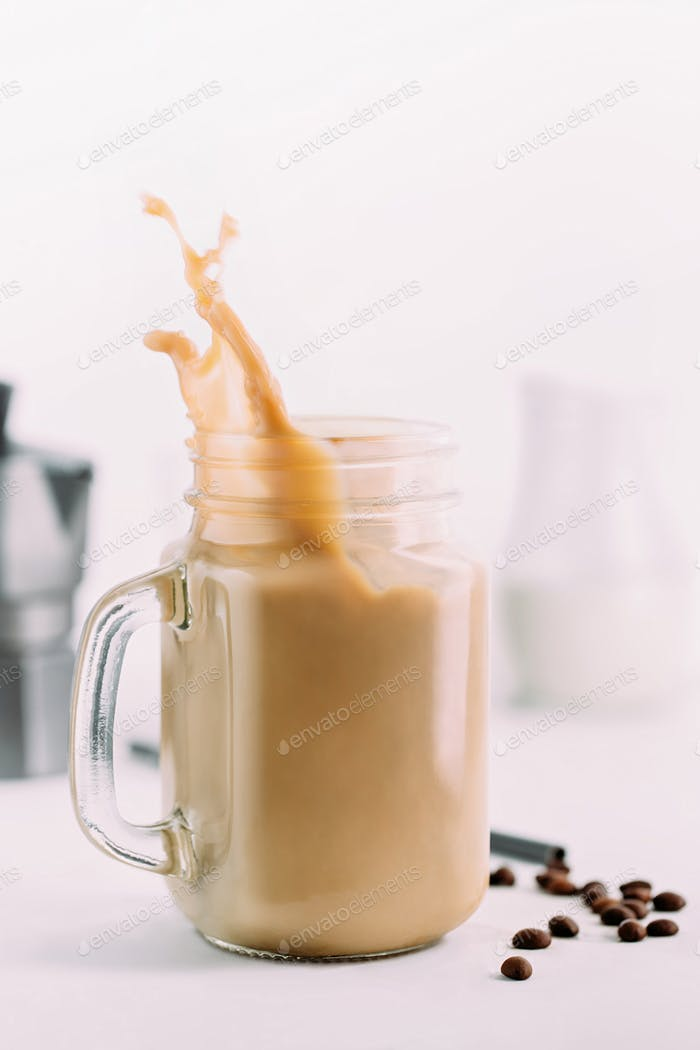 Spritzer von kaltem Kaffee in Glas und Kaffeebohnen.