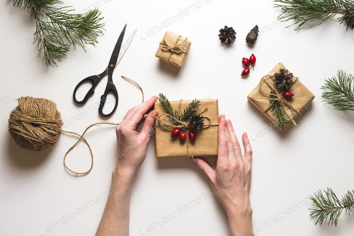 Christmas composition. Female hands packing christmas gifts