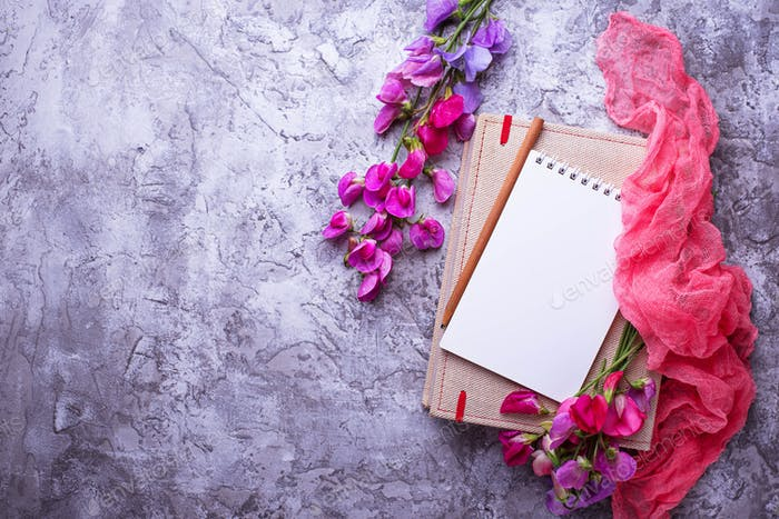 Open empty notebook and flowers.