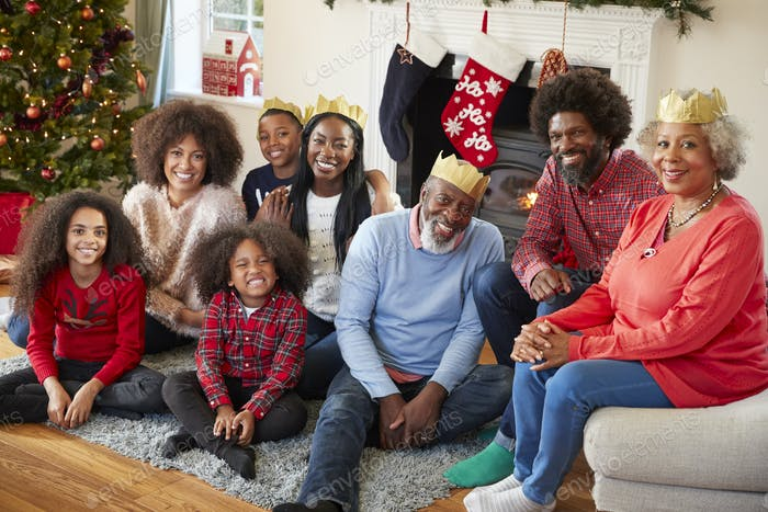 Portrait Of Multi Generation Family Sitting In Lounge At Home On Christmas Day
