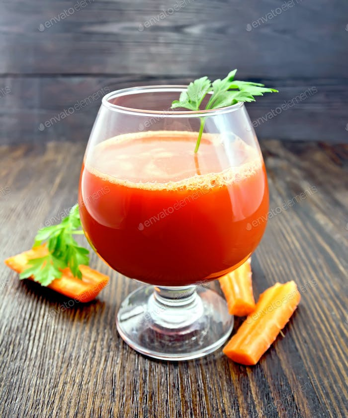 Juice carrot with parsley in wineglass on board