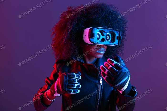 Curly dark haired girl dressed in black leather jacket and gloves uses the virtual reality glasses