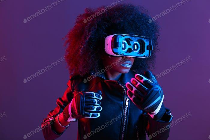 Curly dunkelhaarige Mädchen in schwarzen Lederjacke und Handschuhe gekleidet verwendet die Virtual Reality Brille