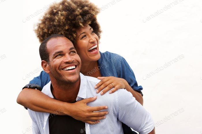 smiling couple standing in embrace on white background