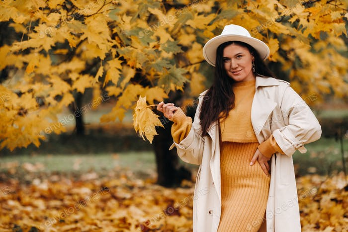 a girl in a white coat and hat smiles in an autumn Park.Portrait of a woman in Golden autumn