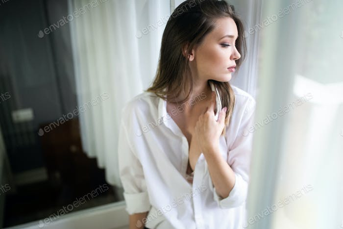 Portrait of a beautiful sensual young woman in white shirt
