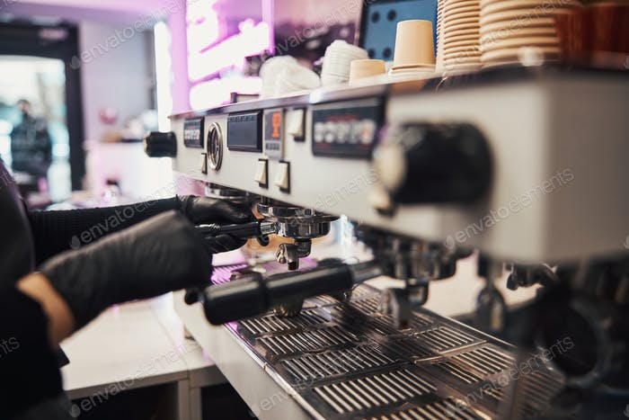 Busy barista operating a modern coffee machine at cafe