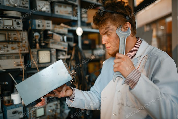 Strange scientist with electric device and wrench