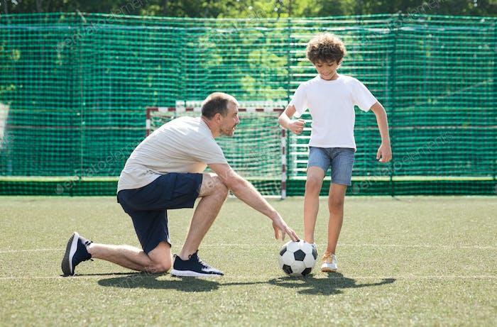Erwachsener Mann, der kleinen Jungen beibringt, wie man Fußball spielt