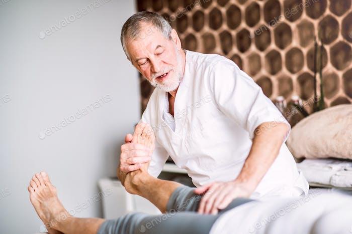 Senior Physiotherapeut arbeitet mit einer weiblichen Patientin.