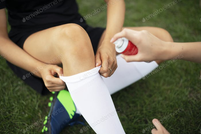 Spraying cooling spray on a football players knee
