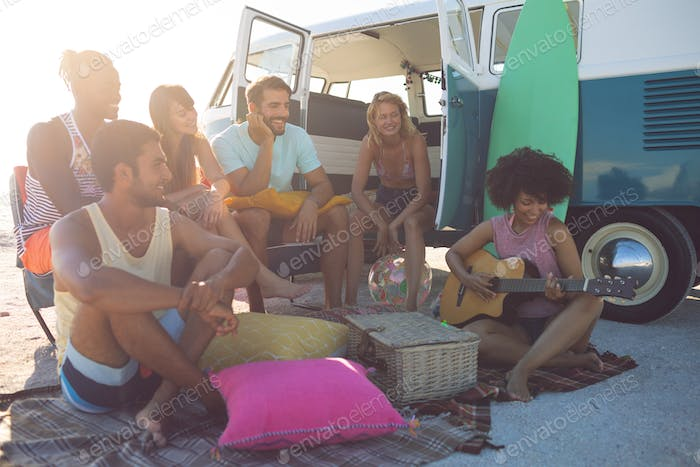 Side view of happy group of diverse friends having fun near camper van at beach