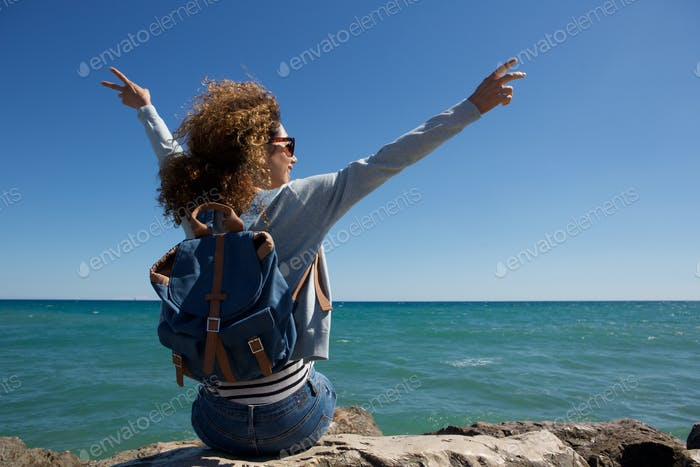 behind of young woman enjoying the seaside with arms raised