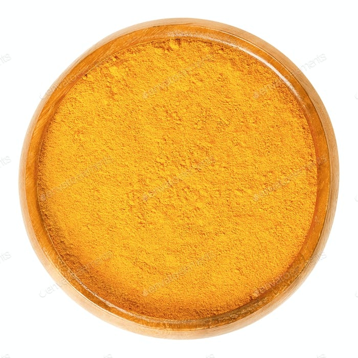 Turmeric powder in wooden bowl over white