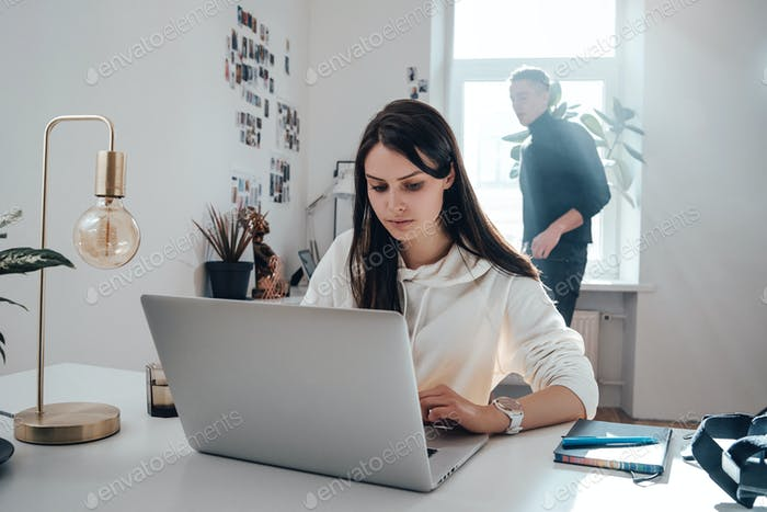 Serious female person works on laptop at desktop in office