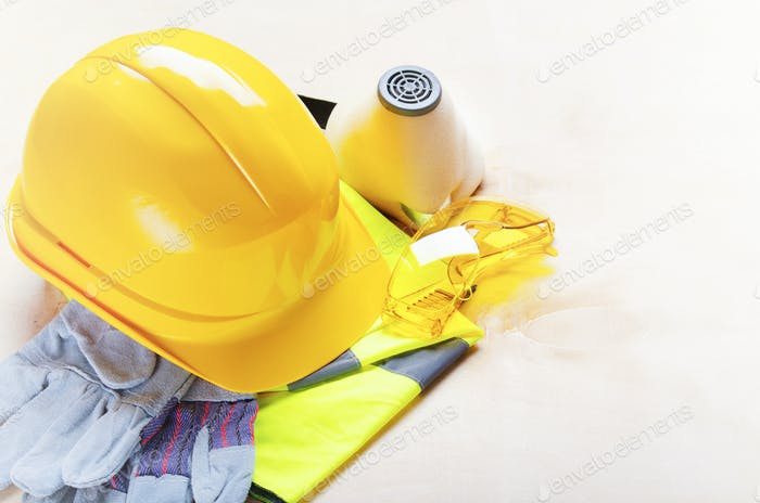 Yellow plastic hard hat, glasses, respirator, reflective vest and protective gloves