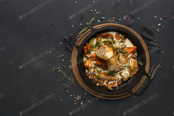 Chicken and vegetables stewed in pot on black background