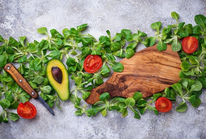 Grüner Hintergrund mit Maissalat, Tomaten und Avocado