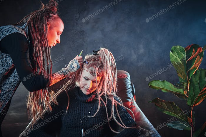 Dreadlocks master is working on client's head