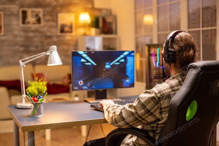 Back view of gamer male playing a shooter on his powerful PC computer late at night in the living