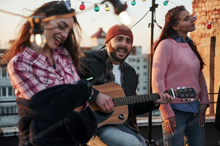 Touching the soul. Three friends enjoy by singing acoustic guitar songs on the rooftop