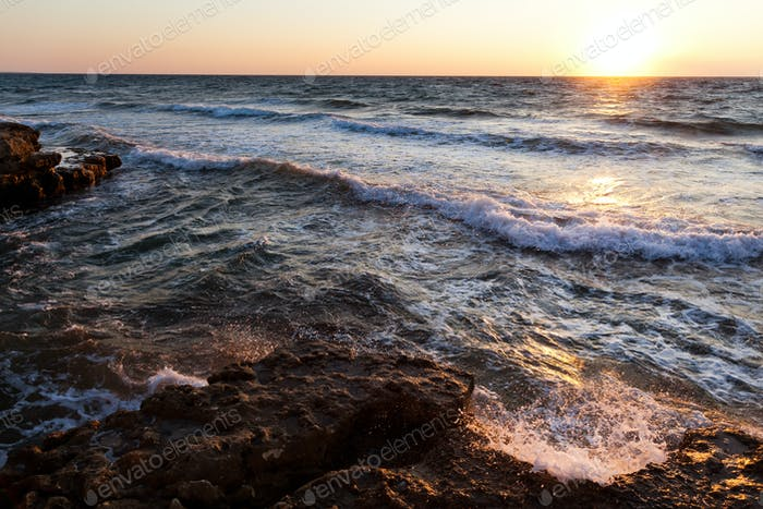 Beautiful sunset over wavy stormy Black sea rocky coastline in Crimea on summer day