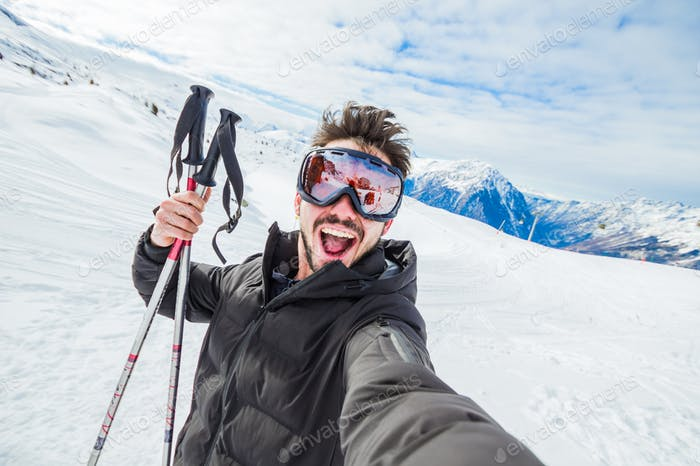 Happy skier taking a selfie at mountains