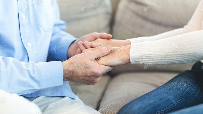 Unerkennbar älteres Paar Hände zu Hause halten