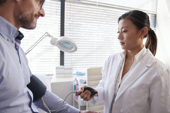 Männliche Patienten mit Blutdruck von weiblichen Arzt in Büro genommen