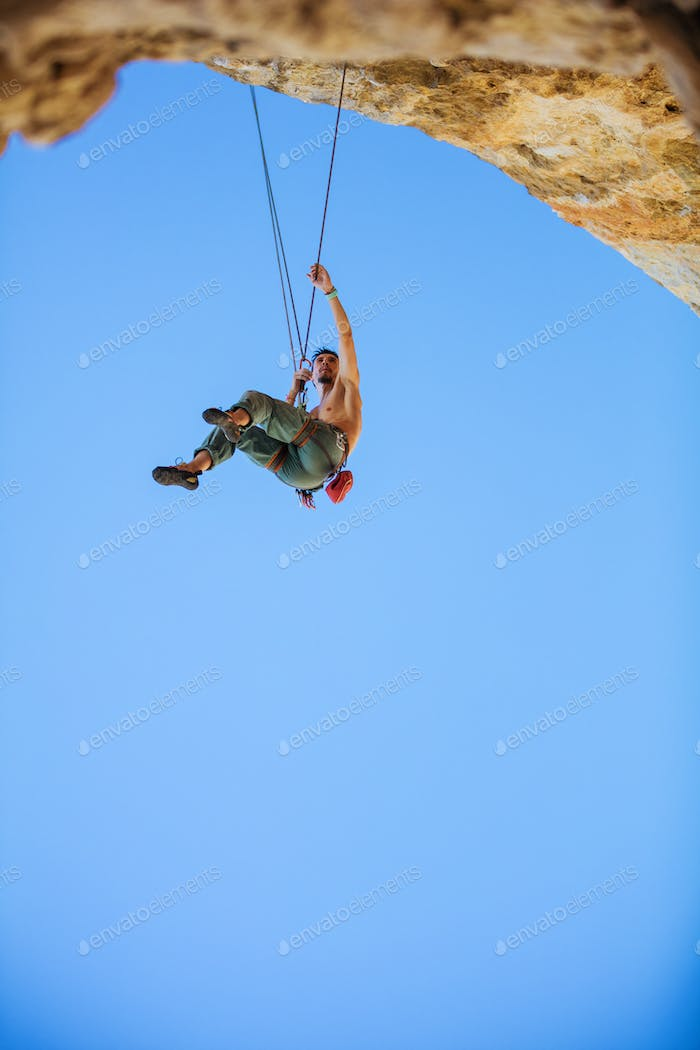 Rock climber hanging on rope while climbing in cave,