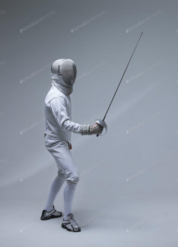 Hombre con traje de esgrima practicando con espada